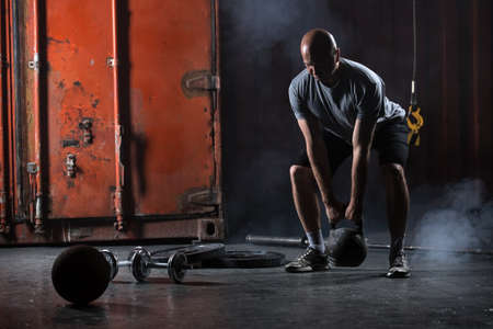 Photo for Bald charismatic athlete doing squats with weights. Studio shot in a dark tone. - Royalty Free Image