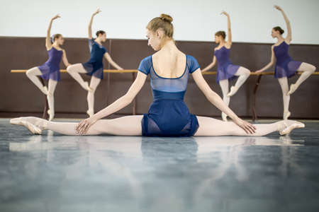 Photo pour ballerina sitting on the floor with his back to the camera in the splits and dance class dancers practicing on the background - image libre de droit