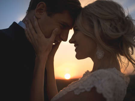 Foto de Close portrait silhouette in love wedding couple. Against the setting sun in the field. Lovers hug, girl tenderly holding her husbands face with both hands, smiling and looking into his eyes. - Imagen libre de derechos