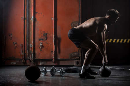 Photo for Beautiful athlete doing kettlebell swings. View from the back. Athlete bare-chested. Studio shot in a dark tone. - Royalty Free Image