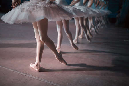 Foto de Dancers in white tutu synchronized dancing on stage. Repetition. - Imagen libre de derechos