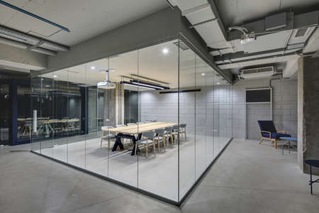 Photo pour Luminous conference zone in the office in a loft style with brick walls and concrete columns. Zone has a large wooden table with gray chairs and glass walls. Above the table there is a projector. - image libre de droit