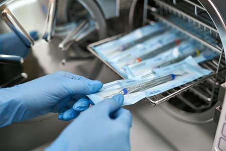 Foto per Dentist is taking dental probe from sterilize machine - Immagine Royalty Free
