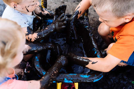Photo pour boy and girl playing in the mud in the summer on the street - image libre de droit