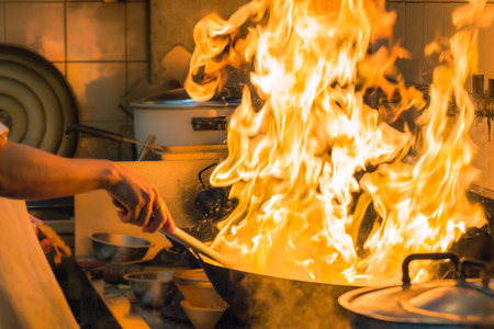 Fire gas burn is cooking on iron pan,stir fire very hot in kitchen