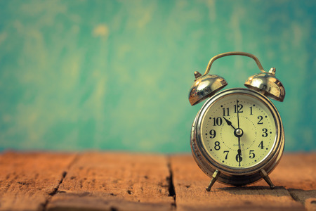 Foto de Vintage background with retro alarm clock on table - Imagen libre de derechos