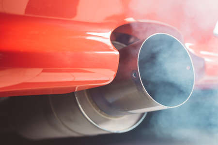 Photo pour Smoke coming out of red car exhaust pipe - image libre de droit