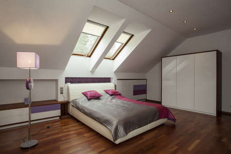 Bright bedroom with wooden floor and violet additions
