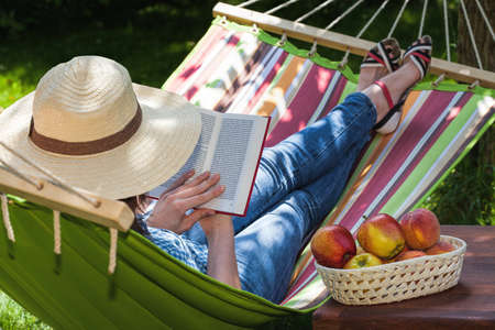 Photo for A woman relaxing on a hammock with a novel - Royalty Free Image