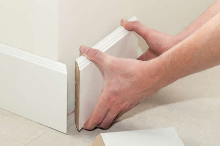 Photo pour Man putting new skirting board in house - image libre de droit