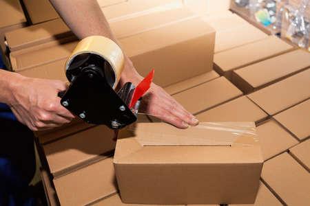 Foto de Worker using adhesive tape to close the boxes - Imagen libre de derechos