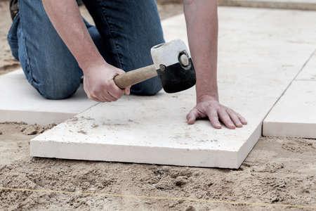 Foto de Installation of paving slabs with a huge hammer - Imagen libre de derechos