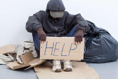 Foto de Homeless man sitting on a street with sign - Imagen libre de derechos