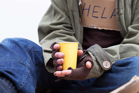 Foto de Hands of homeless person holding a yellow, paper cup - Imagen libre de derechos