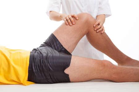 Physiotherapist massaging and examining injured leg