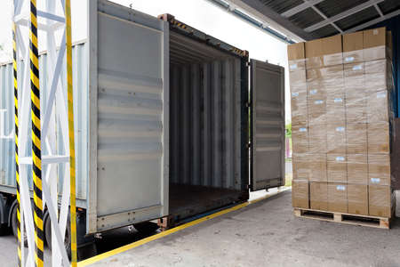 Foto per Forklift with carton boxes loading the truck - Immagine Royalty Free
