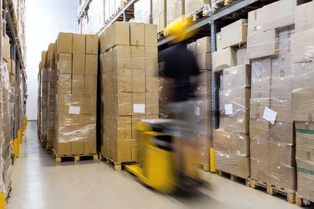 Foto de Fork lift with operator working in warehouse - Imagen libre de derechos