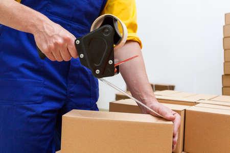 Foto de Closeup of a worker hands packing a box - Imagen libre de derechos