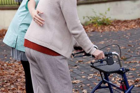 Foto de Nurse helping elder person to walk with walker - Imagen libre de derechos
