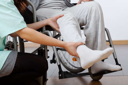 Photo pour Young physiotherapist exercising with elder disabled person - image libre de droit