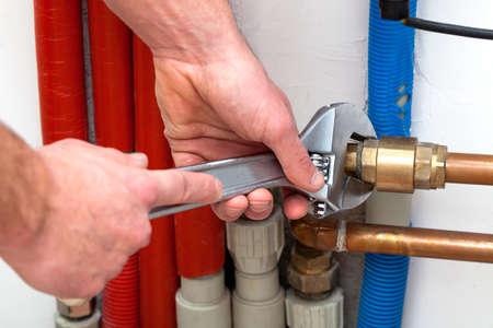 Photo pour Man's hands with wrench turning off valves - image libre de droit