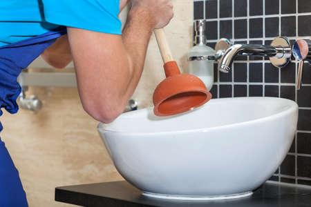 Foto de Plumber with rubber plunger in a bathroom - Imagen libre de derechos