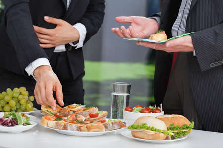 Photo pour Business people discussing at the lunch buffet - image libre de droit