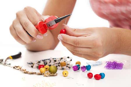 Photo pour A person designing colorful earings with plactic beads - image libre de droit