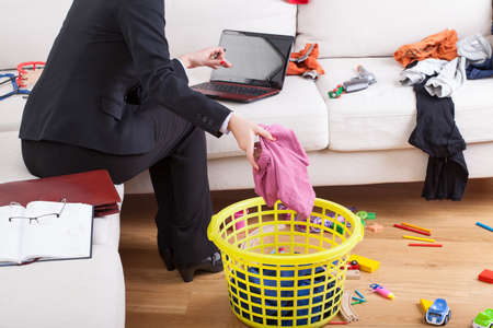 Photo pour Active businesswoman cleaning house and working on computer in the same time - image libre de droit