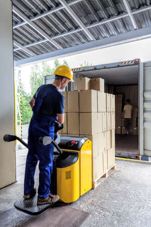 Photo for Warehouse export of the articles in packages doing by a worker - Royalty Free Image