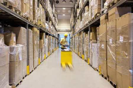 Photo for Warehouse worker with a yellow hand pallet truck - Royalty Free Image