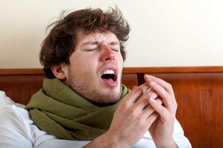 Foto de Man with sinus infection sneezing in bed - Imagen libre de derechos