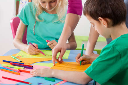 Foto de Children develop their creativity by drawing with art teacher - Imagen libre de derechos