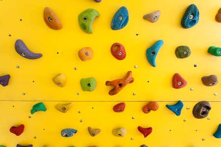Foto de Yellow climbing wall with colorful rocks - Imagen libre de derechos
