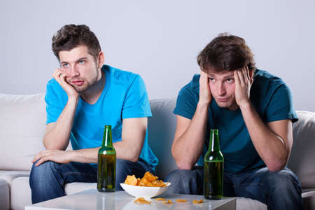 Photo for Two friends bored over bottles of beer and nachos - Royalty Free Image