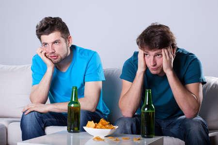 Foto de Two friends bored over bottles of beer and nachos - Imagen libre de derechos