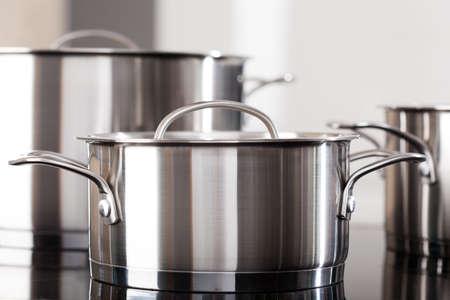 Foto de New clean aluminum pots on the kitchen top - Imagen libre de derechos