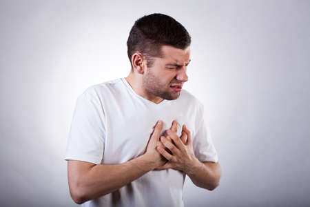 Foto de Young man in white t-shirt with strong heart attack - Imagen libre de derechos
