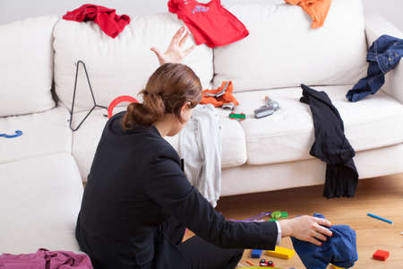 Foto de An angry woman in a room full of clothes all over the place - Imagen libre de derechos