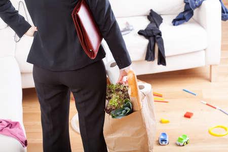 Foto de An elegant woman with grocery shopping left in a messy home - Imagen libre de derechos