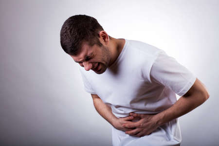 Photo for Young man with severe stomachache holding his stomach - Royalty Free Image