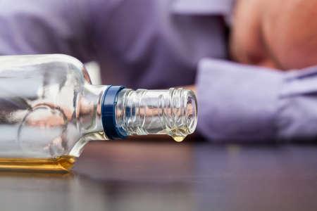 Foto de Drunk man sleeping with almost empty bottle of alcohol - Imagen libre de derechos
