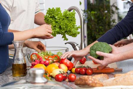 Foto de Friends cooking together the veagetarian dinner in kitchen - Imagen libre de derechos