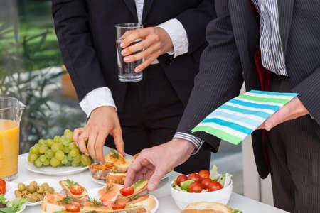 Foto de Business people eating lunch at office buffet - Imagen libre de derechos