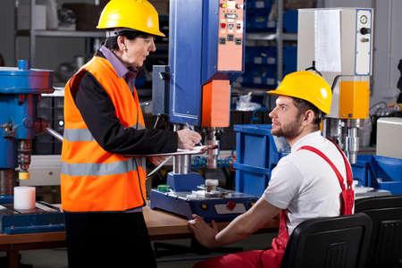 Foto de Elder female superior is instructing young male worker - Imagen libre de derechos