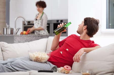 Photo pour Couch potato doesn't help his wife, horizontal - image libre de droit