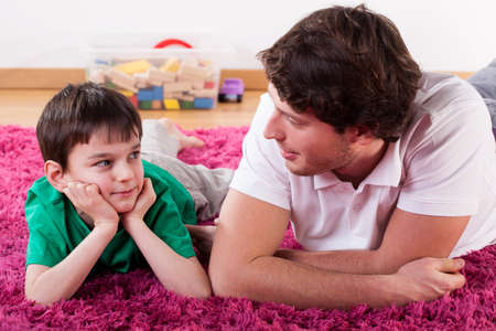 Photo for A young handsome dad lying on the floor with his son - Royalty Free Image