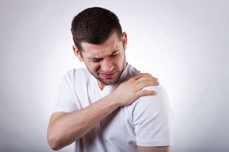 Photo pour Young attractive man having shoulder pain - image libre de droit