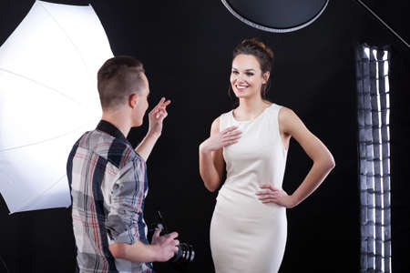 Photo for Photpgrapher telling compliment to his model during photoshooting - Royalty Free Image