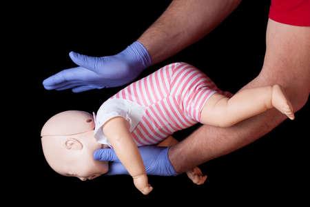 Foto de Doctor showing first aid for choking infant - Imagen libre de derechos